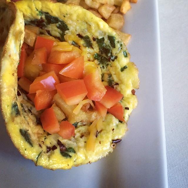 Egg burrito, spinach, onions, tomatoes, red bell peppers, crushed red peppers, homemade hashed potatoes, natural cheese